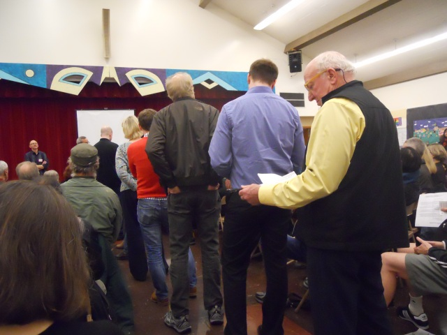 People line up to express their concerns at a community meeting.